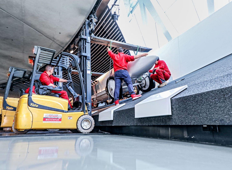 Der Blitzen-Benz wird mithilfe eines Gabelstaplers an vier Seilen in Position gebracht.