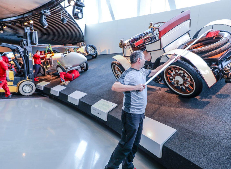 Ein Mitarbeiter des Mercedes-Benz-Museums pflegt und reinigt die Fahrzeuge
