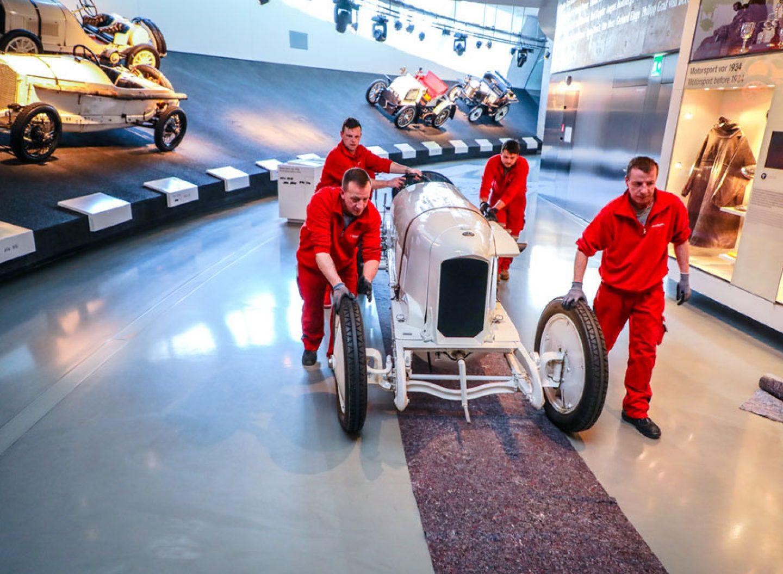 Blitzen Benz wird von Mitarbeitern zu seinem Ausstellungsort geschoben