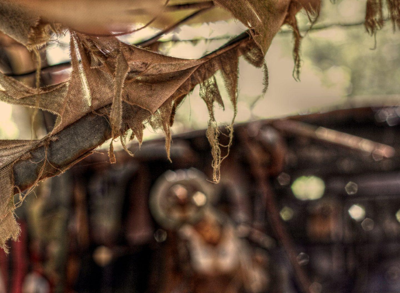 Stofffetzen als Leinen hängen in einem Autowrack
