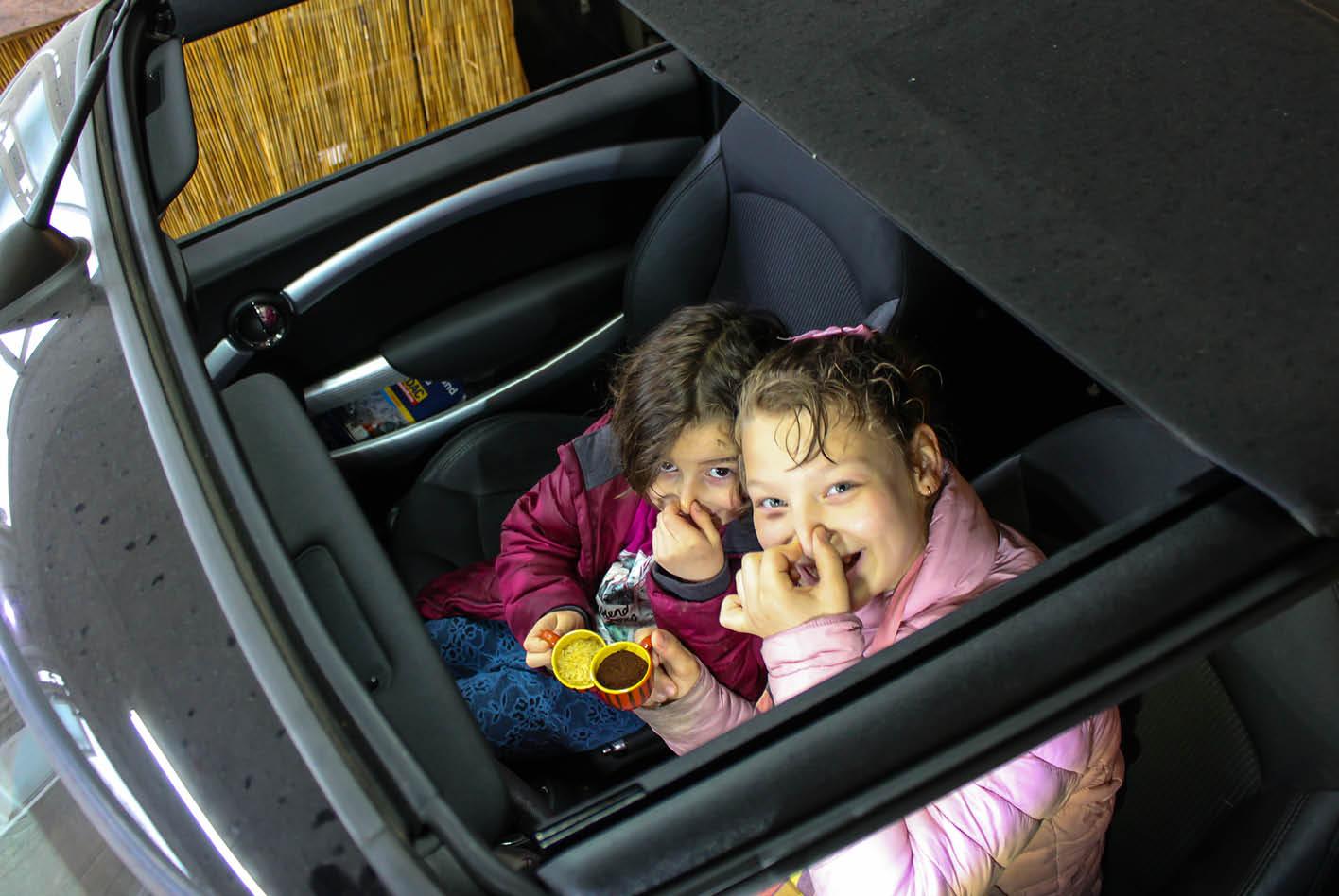 Kinder auf den Vordersitzen mit einer Tasse Kaffee und Reis in der Hand. Hilft gegen Gerüche.