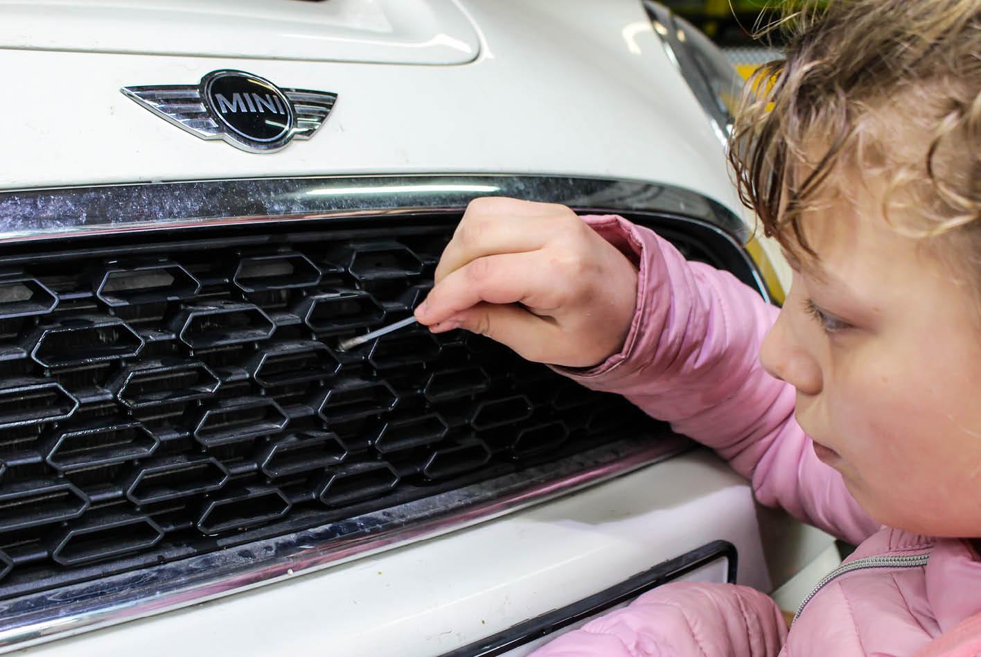 Kind reinigt den Kühlergrill mit einem Ohrenputzstäbchen.