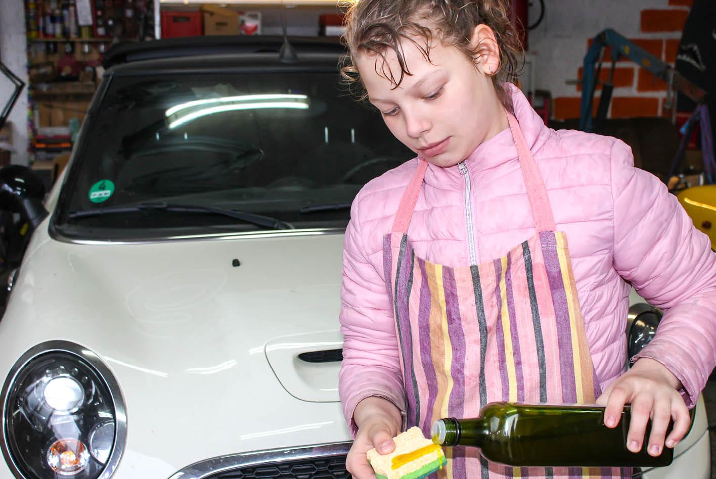 Ein Kind benetzt einen Schwamm mit Öl