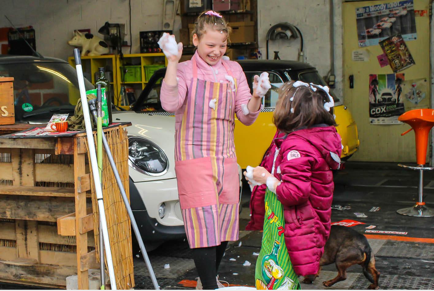 Zwei Kinder machen eine Schaumschlacht vor dme Auto.