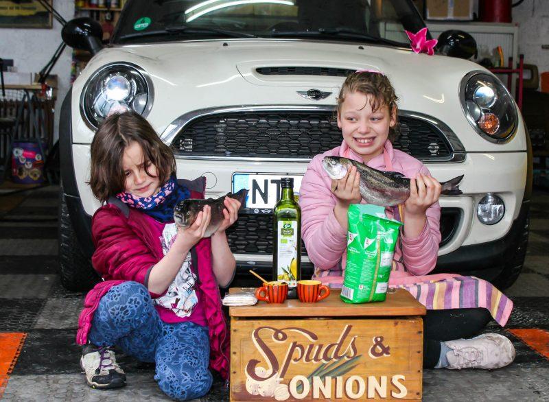Kinder sitzen vor einem Auto und haben frische Fische in der Hand.