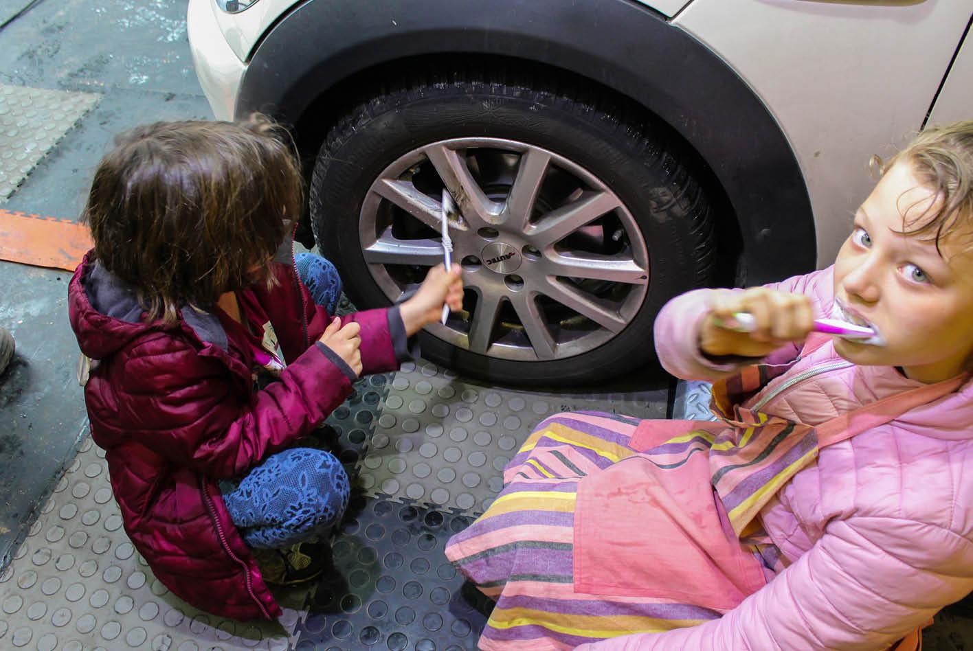 Kinder reinigen die Autofelgen mit ausgedienten Zahnbürsten.