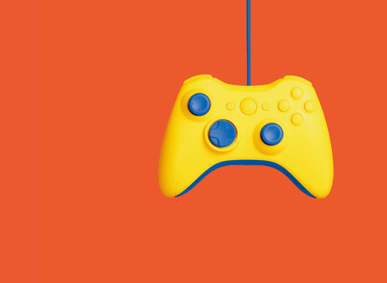 Ein gelber Controller für Videospiele, der am blauen Kabel hängt.