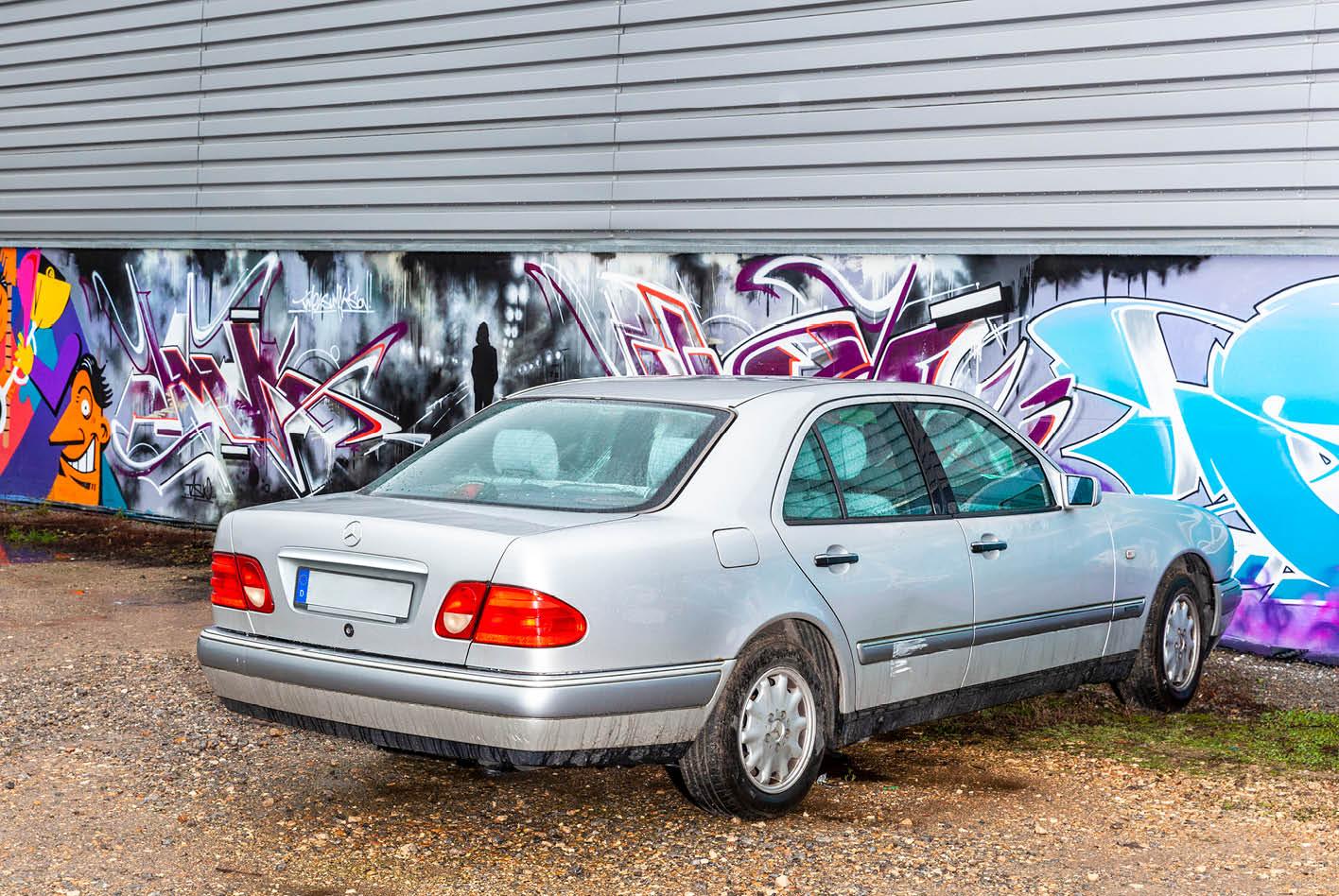 Unbuntes Auto trifft auf bunte Wand. Bei Autofarben geht der Trend zu mehr Grau, Schwarz und Weiß.
